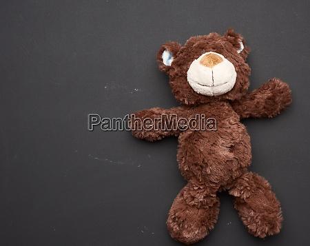 brown teddy bear on a black