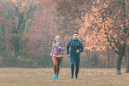 couple in wonderful fall landscape running