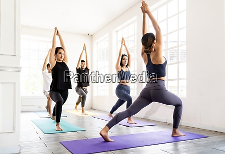 asian sporty people practicing yoga in