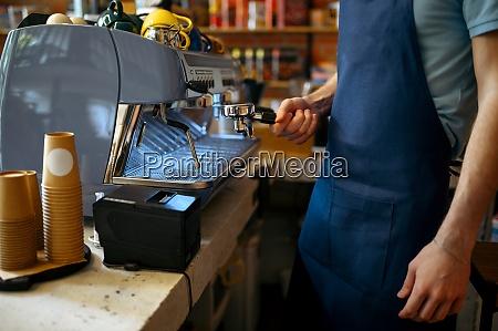 male barista in apron prepares coffee