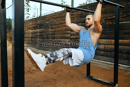 muscular man doing abs exercise street