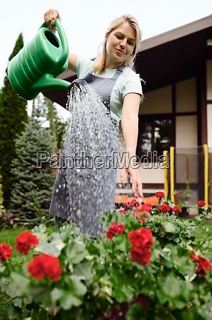woman in apron watering flowers in