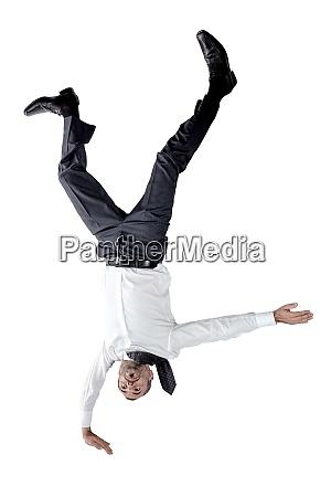 businessman upside down balancing on one