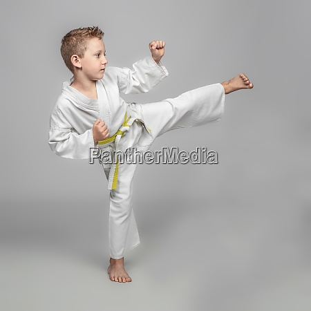 child practicing karate in kick position