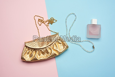 golden clutch bag with various cosmetics