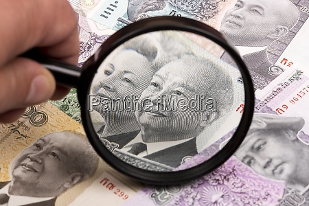 cambodian riel in a magnifying glass