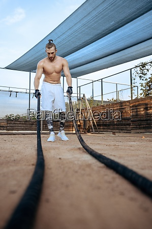 muscular man doing exercise with ropes