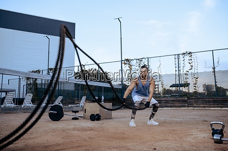 athletic man with ropes street workout