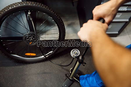 bicycle assembly in workshop man inflates