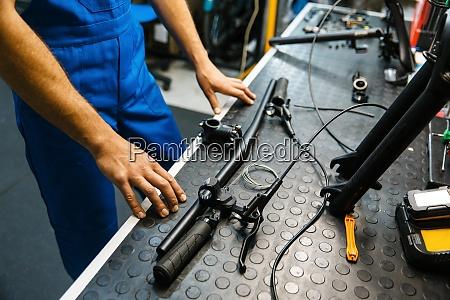 bicycle assembly man installs handlebar