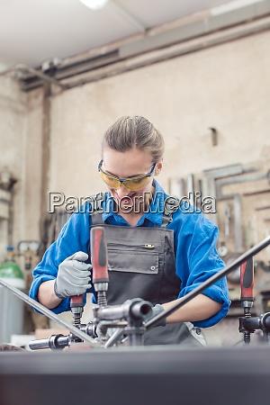 woman in metal workshop with tools