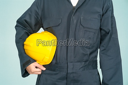 worker standing in blue coverall holding