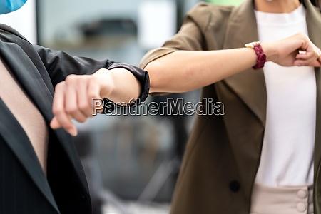 businesswomen wear face mask elbow greeting