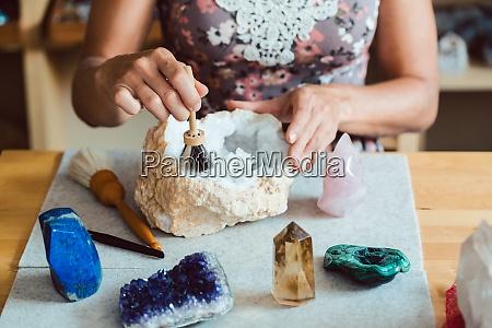 woman brushing and dusting various gemstones