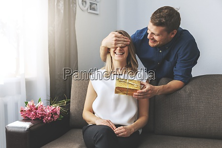 husband giving romantic surprise gift to