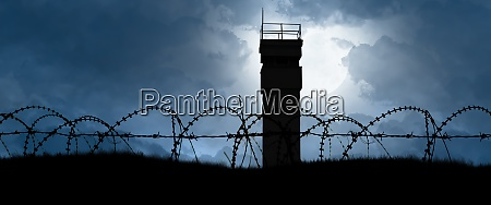 watchtower behind barbed wire as a