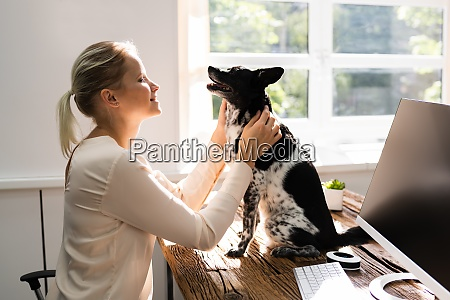 woman hugging dog in home office