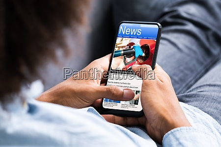 african american holding mobile phone reading