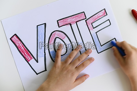 childs hands coloring vote sign