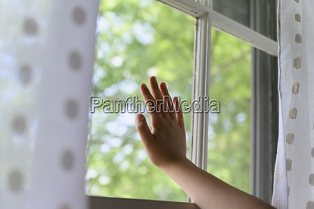 childs hand touching window with trees