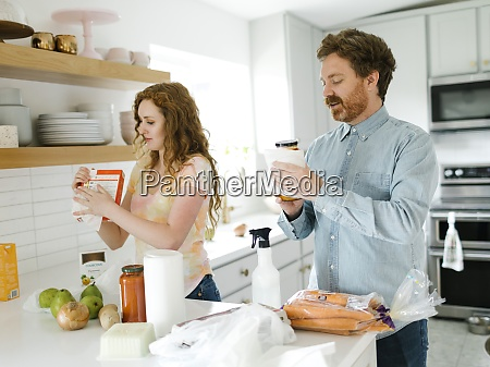 man and woman cleaning groceries in
