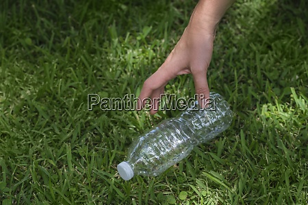 womans hand picking up plastic bottle