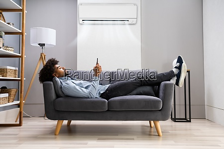young man lying under air conditioner