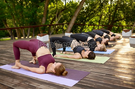 sportive women on group yoga training