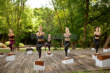 slim women doing balance exercise group
