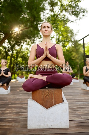 women relax in yoga pose group