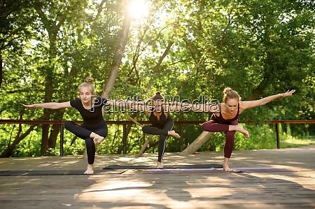 three women doing balance exercise group