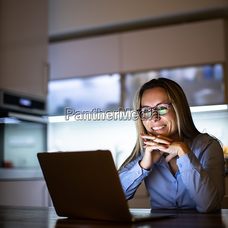 middle aged woman working late in