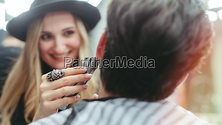 barber woman trimming beard of client