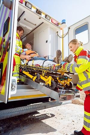 paramedics putting injured man on stretcher