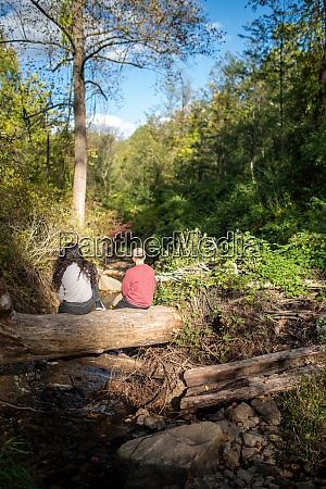 two people rest on a log