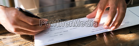 african writing money cheque sign check