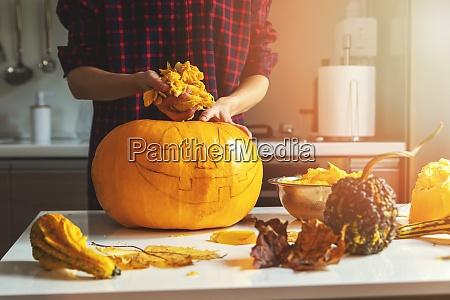 woman prepare pumpkin for halloween holiday
