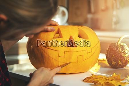 woman carving pumpkin into jack o