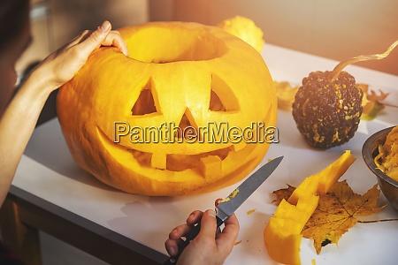 carving pumpkin into jack o lantern