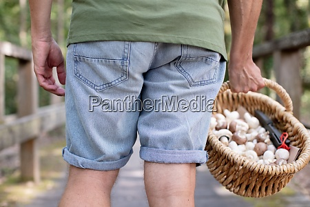 man holds a wicker basket full