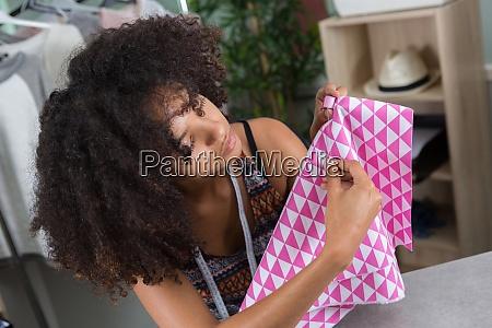 female dressmaker putting thread into needle