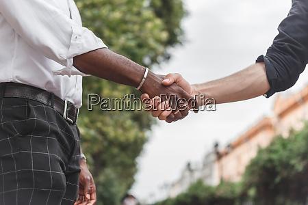 handshake between african and a caucasian