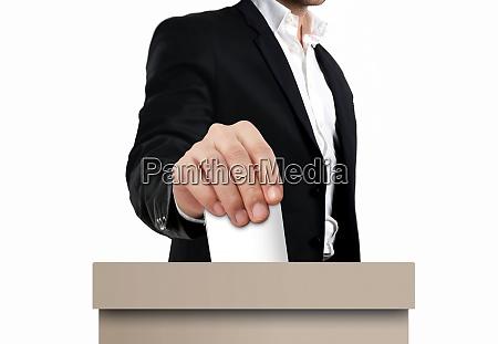 man hand putting ballot paper into
