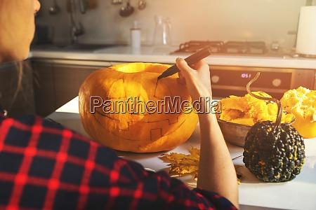woman painting face on halloween pumpkin