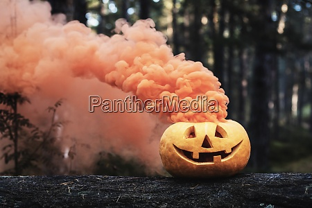 carved halloween pumpkin with orange smoke