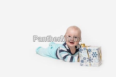 smiling toddler boy is lying next