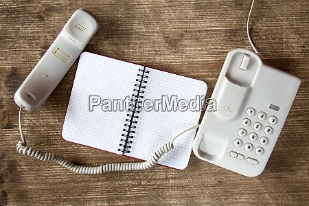 grey telephone and blank notebook