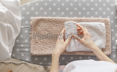 woman rolling ironed clean towels standing