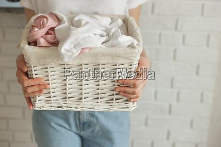 woman holding wicker basket with heap