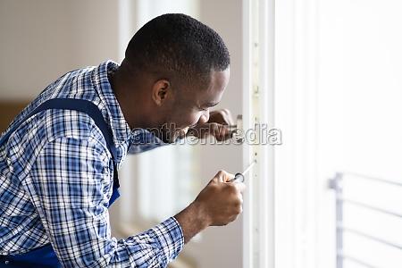 african repairman in overalls installing window